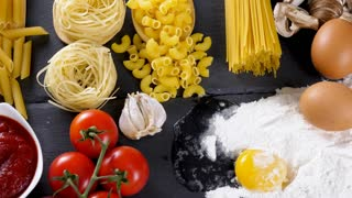 Raw pasta, macaroni and spaghetti next to other ingredients for dinner on dark table