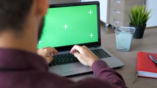 Revealing shot of businessman at home typing and working on a laptop with green screen mock up. Dolly slide 4K footage with parallax effect