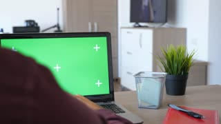 Revealing shot of man working on the computer with a chroma green screen mock up in his house. Dolly slide parallax 4K footage