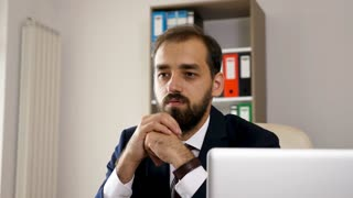 Sad, tired and exhausted businessman close up portrait sitting in his office looking away.