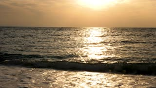 Sea at the sunrise with sun rays reflection in the water. Slow motion footage