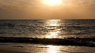 Sea at the sunrise with sun rays reflection on the water. Slow motion footage