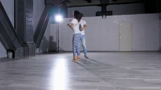 Sexy couple of professional dancers dancing in big empty room. Sport and healthy lifestyle