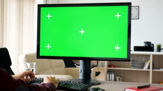 Side view of man sitting in front of computer with big green screen mock-up chroma typing on the keyboard. He is in the living room of his house. Dolly slider 4K footage with parallax effect