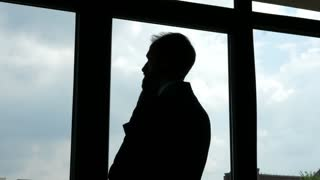 Silhouette of a businessman looking outside the windows in his office. Carrier, succes and worried. Dolly parallax moving shot.