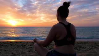 Silhouette of woman sitting on the beach practicing yoga at the sunrise. Relaxation and meditation.
