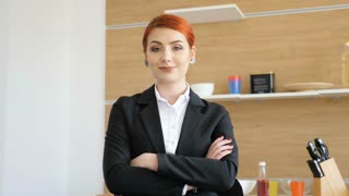 Slow motion footage of portrait of beautiful businesswoman home but still dressed in formal suit smiling to the camera