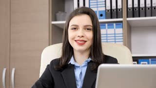 Slow motion of bussineswoman in her office looking at the camera and smiling. There is a shelf packed with files and other items in the background. This video can be used as a supplemental footage
