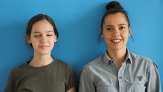 Slow motion of younger and oldest sister looking at each other and laughing on blue background in studio