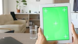 Slow sliding over a digital tablet PC with green screen chroma mock-up in comfy living room in the house.