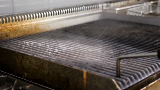 Spraying water and cleaning a grill in restaurant kitchen