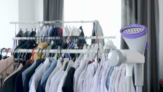 Steam iron steaming with a lot of clothes on hanger in the background. 4K resolution footage