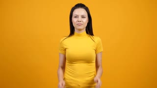 Surprised cheerful woman closes her eyes then starts jumping from happinnes and excitement. Funny slow motion footage on yellow background