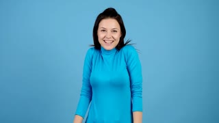Surprised girl winks at the camera, makes ok sign then shows thumbs up on blue background. Young adult making gestures and smiling.