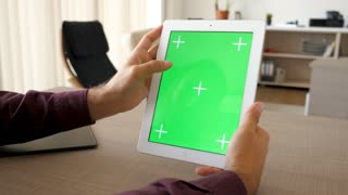 Tablet PC in vertical position with green screen chroma mock-up beeing hold by male hands on the desk in house