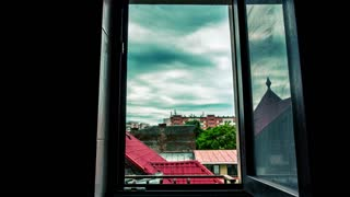 Time lapse of moving dark clouds over the city through a window. Cinematic grading