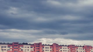 Timelapse moving clouds over city buildings. Urban cityscape