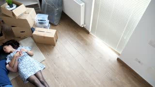 Top view couple lying down on the floor of their new house. They are surrounded by cardboard boxes and furniture. They are happy and talk to each other making plans for future