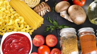 Top view delicious variety of pasta and other ingredients for dinner on dark table. Dolly slide footage