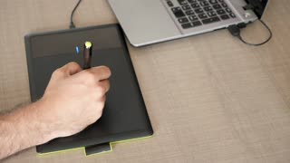 Top view of graphic artist hand drawing on a digital tablet on a desk. Artist at work