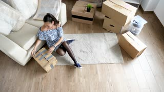 Top view woman unpacking from cardboard boxes while her husband is moving furniture to their new house