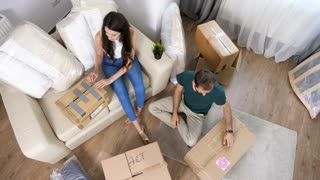 Top view young couple unboxing from cardboard boxes in their new house