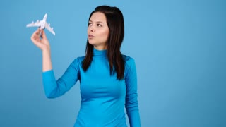 Travel concept of woman playing with a toy airplane on blue background. Freedom and happiness