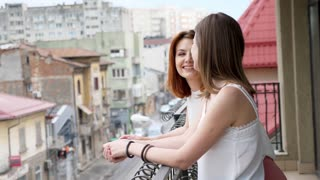 Two beautiful and young women talking and laughing at balcony. Slow motion