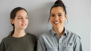 Two beautiful sisters embracing each other and smiling on gray background. Slow motion footage