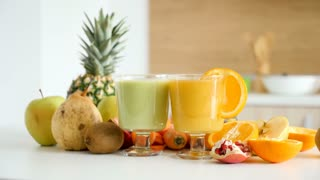 Two glasses with healthy and organic juices in the kitchen next to the fruits and vegetables it was made of. Detox and health.