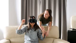 Two sisters having a lot of fun in the living room with a virtual reality headset