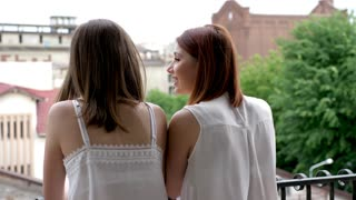Two women looking at each other and laughing. Slow motion. Shot from behind
