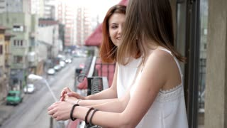 Two women smiling and laughing on balcony. Slow motion