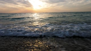 Waves in the water in the sea at the sunrise. Sceninc landscape. Runing on the beach