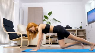 Woman does sport at home. She is doing exercises for legs muscle on a blue mat in linving room of her home. She is a beautiful arabian mixed race young woman. Dolly slider 4K footage