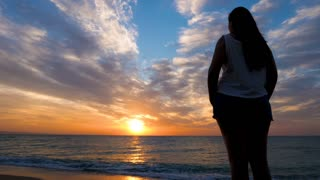 Woman in silhouette admiring a beautiful sunrise over the sea on the beach. Travel and relaxation