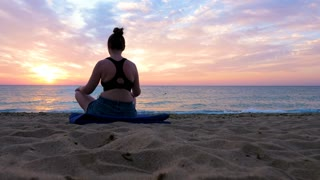 Woman practicing yoga on the beach at the sunrise looking at a scenic panorama. New beginnings and perspectives