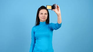 Woman vlogger talking to a camcorder on blue background. Blog and lifestyle