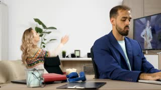 Woman watches TV and makes noise in the background while her husband tries to work on the laptop in the same room. He puts the headphones on to escape the fuss. Rack focus dolly slider 4K footage