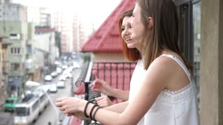 Women on the balcony laughing and talking. Slow motion