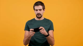 Young attractive man playing a video game on his smartphone isolated on yellow orange background. Funny person enjoying his leisure time
