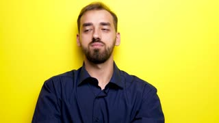 Young beautiful man looks at his right and left them makes the silence gesture by bringing his finger to the mouth. Close up footage over yellow background