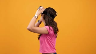 Young beautiful woman experiencing VR technology with virtual reality goggles on yellow orange backgorund. Happy young woman with modern technology device, Slow motion footage
