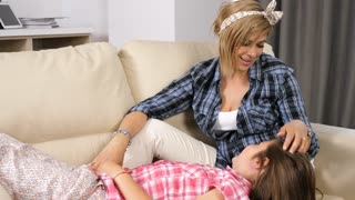 Young mother with her teenage girl in her arms, lying on the couch and talking to each other