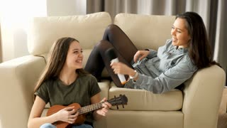 Younger and older sister singing in the living room. One is playing at the ukulele while the other is singing at a microfone on the couch
