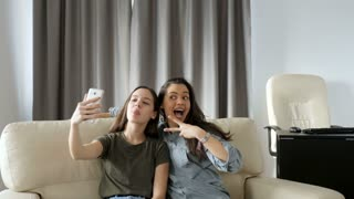 Youngest and older sister taking a selfie on the couch in the living room
