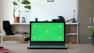 Zoom in on green screen mock up laptop on a desk in the living room