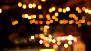 Zoom in on light bokeh defocused over a dark background. City lights