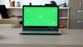 Zoom in shot on a computer screen with chroma mock up on a desk in the living room.