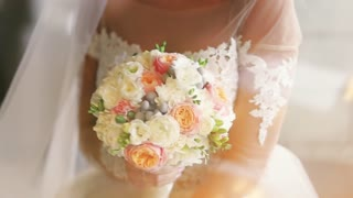 Amazing bride is holding elegant wedding bouquet, colorful flowers. Bride in a white wedding dress in a vail and accessories is holding a wedding bouquet waiting for a bridegroom. Female portrait.